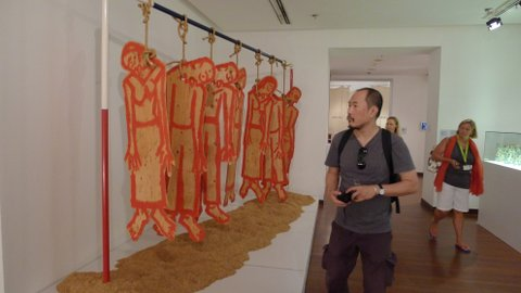 Vasan Sitthiket highlighting the plight of Thai farmers through an installation Committing Suicide Culture: The Only Way Thai Farmers Escape Debt (1995), featuring wooden cutouts of farmers hanging by the noose on a pole painted in Red white and blue, the Thai National colours, hovering over mounds of rice husks. Exhibited at Negotiating Home, History, Nation.